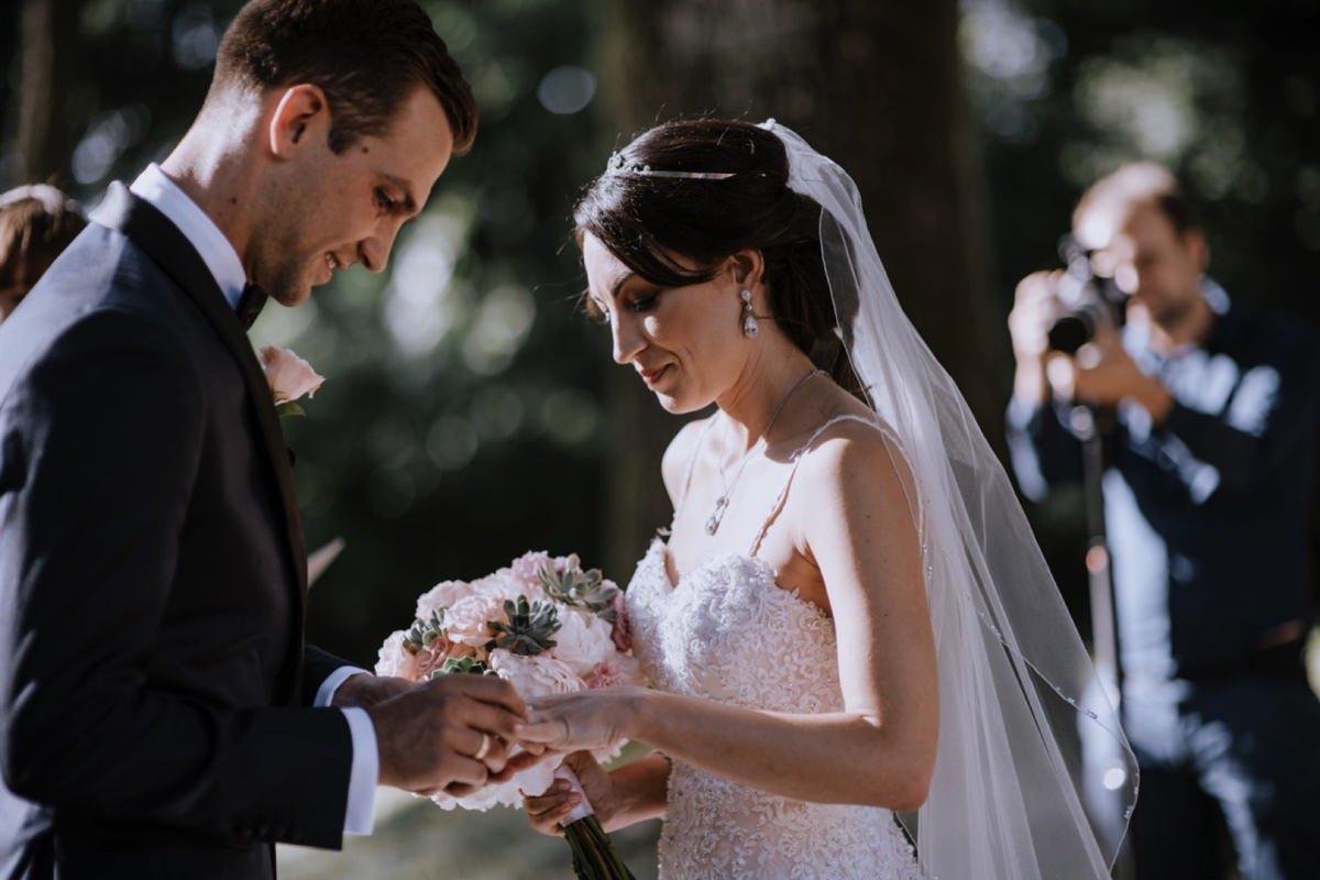 Zakładanie obrączek podczas ceremonii ślubnej w plenerze