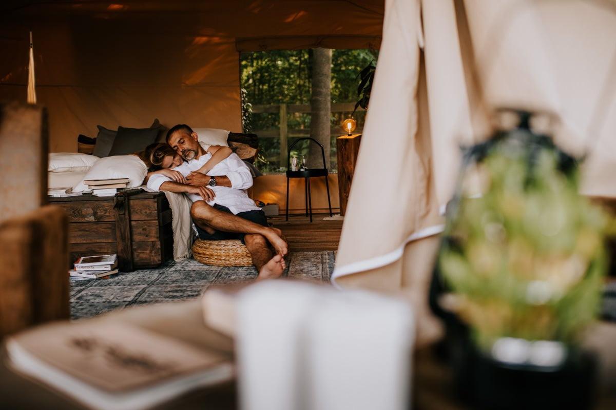 Kobieta i mężczyzna leżą na łóżku w namiocie w Kimura Glamping Cicha 23 na sesji narzeczeńskiej