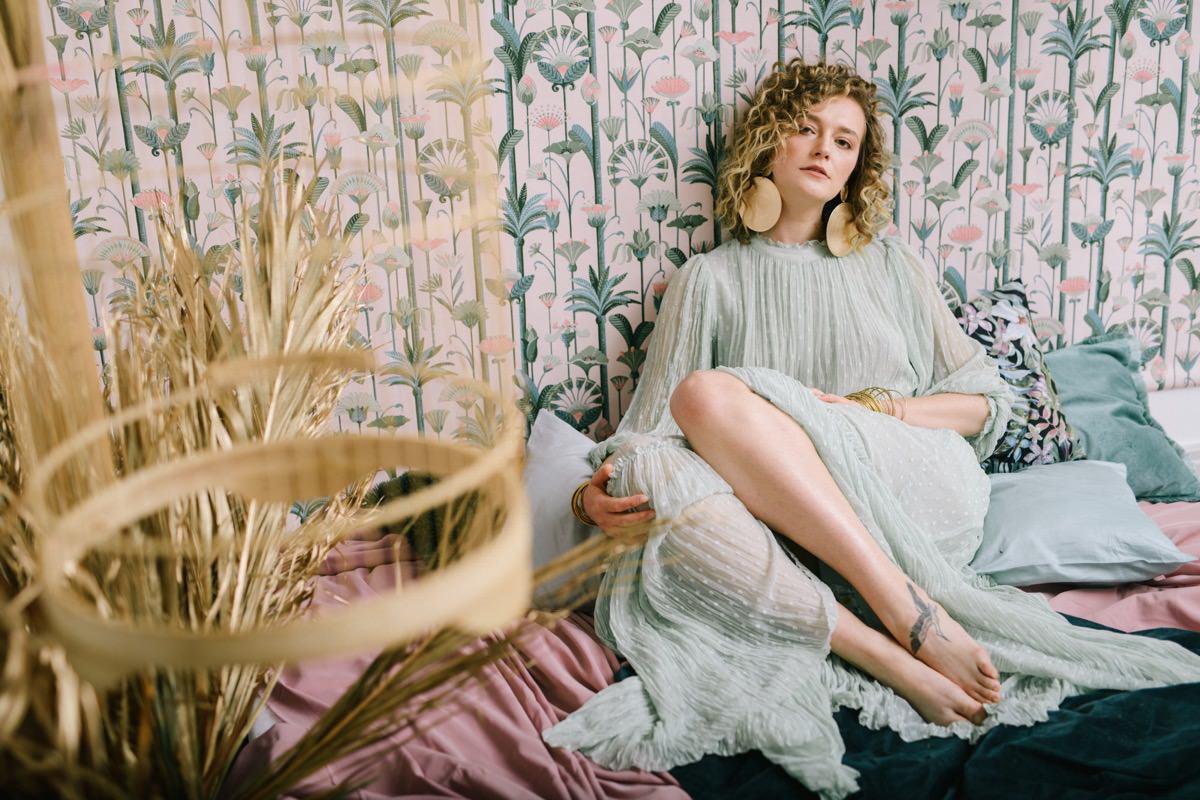 kobieta relaksuje się na łóżku w promieniach słońca, sesja kobieca